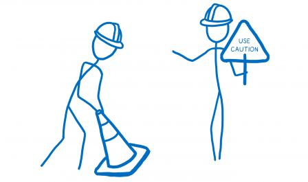 Deux bonhommes sont en train de placer des plots de chantier et l'un tient un panneau avec 'À utiliser avec précaution'.